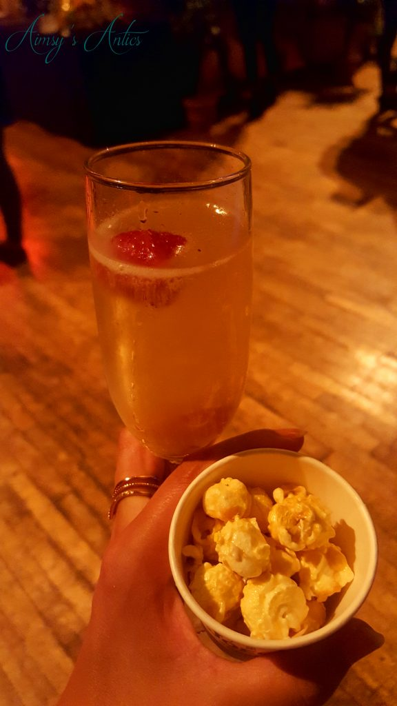 Champagne cocktail in hand with small pot of popcorn