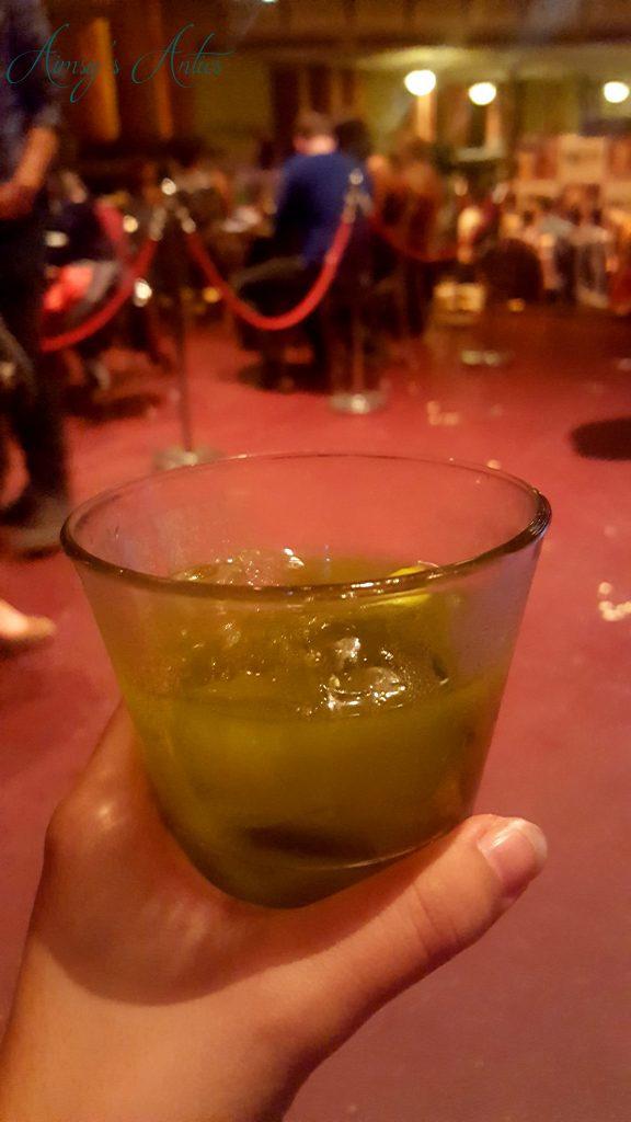 Green coloured cocktail being held in a hand