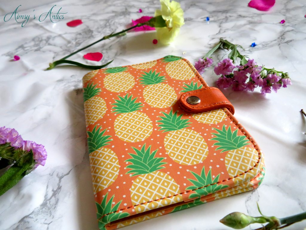 Pineapple passport cover with flowers around it