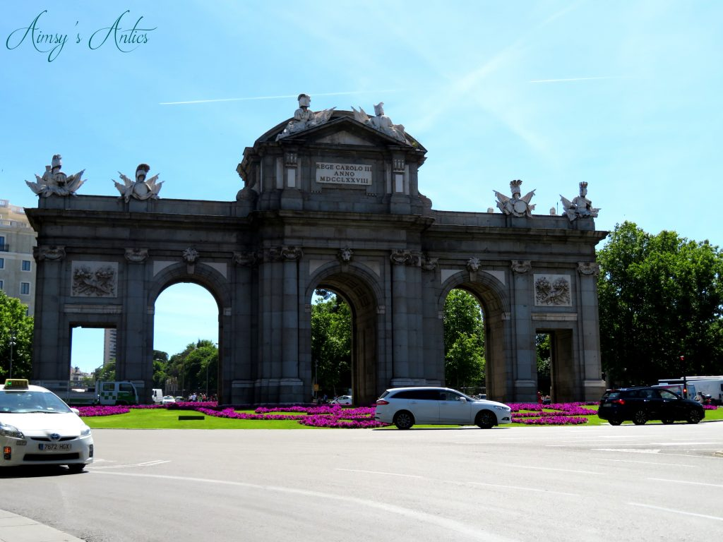 Archway infront of Retiro Park with pink flowers and a car