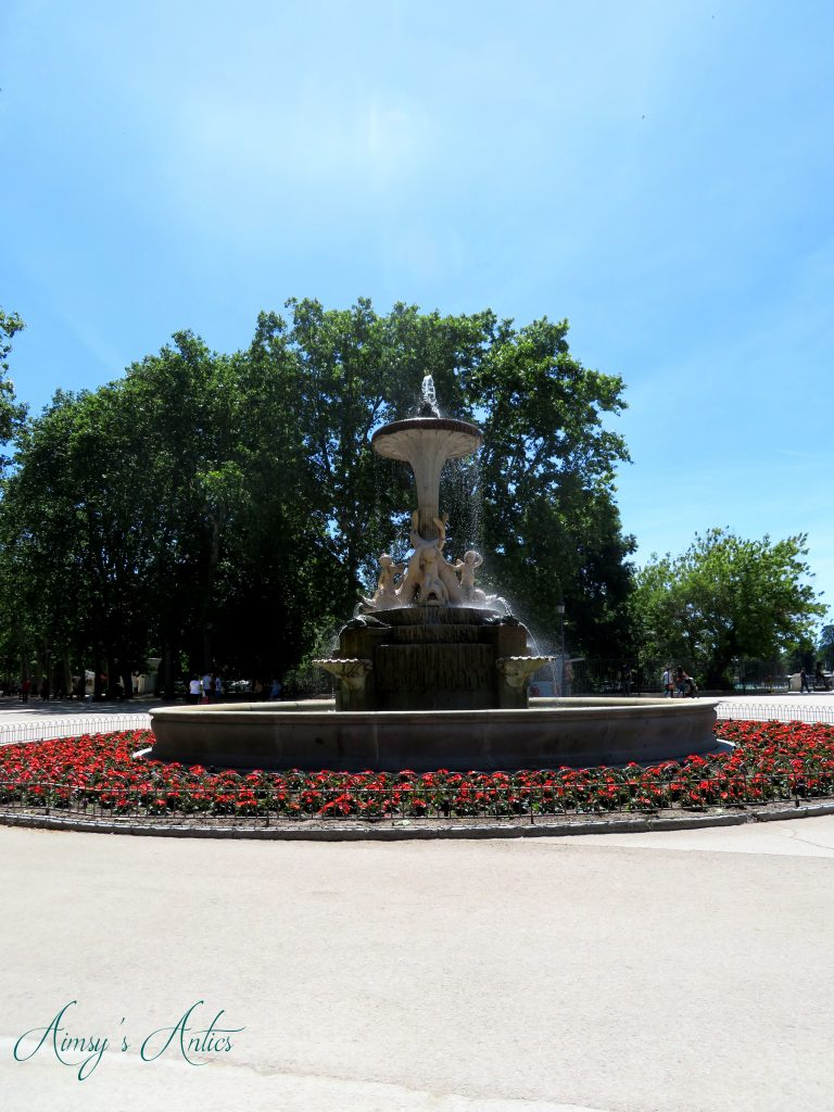 Fountain in Retiro Park with red flowers around it