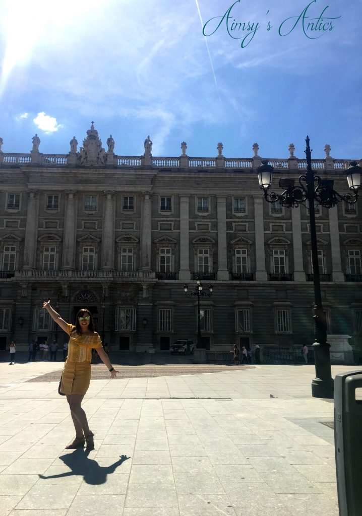 Woman stood with arms in air in front of Royal Palace, Madrid