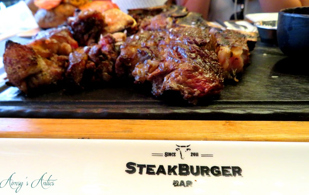 Steak meat on a board with 'Steakburger' placemat